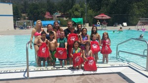 BBBS Summer Splash - group poses with True Value backpacks in Oakhurst 2015 at YHS Pool