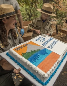 "October 1, 2015: Gabriel Lavan-Ying, better known as ""Ranger Gabriel"", cuts a commemorative Anniversary cake at the conclusion of Yosemite National Park's 125th Anniversary celebration. Ranger Gabriel is pictured with Yosemite National Park Ranger Kristen Kosick. Approximately 1500 people attended the ceremony today in Yosemite Valley. (Al Golub/NPS)"