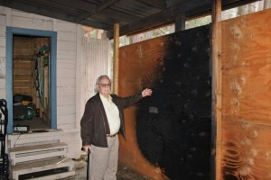 George Hathaway shows his burned carport - photo by Bill Ritchey