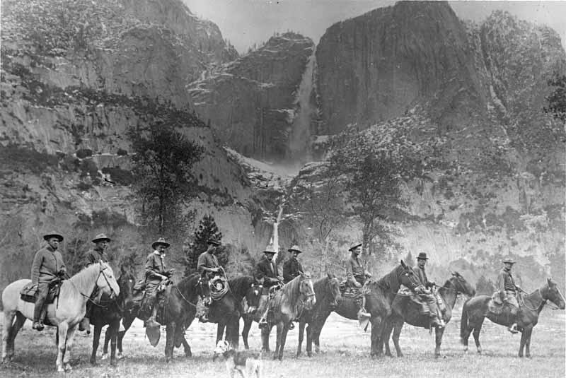 Nine park rangers called the first rangers of Yosemite National Park, shown mounted on horses lined up in meadow in Yosemite Valley, 1915; with Yosemite Falls in distance, and dog in foreground. Left to right, Oliver Prien, Chief Ranger; Charles Bull, Assistant Chief Ranger; Jack Gaylor, Second Assistant to Chief Ranger; Wayne Westfall; George McNab; Charles Leidig, first park ranger in Yosemite; Charles Adair; Archie Leonard; Forest Townsley (YOSE023451)