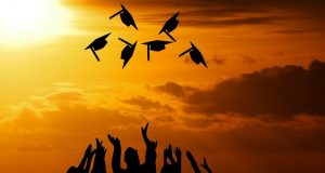 Picture of graduation caps being thrown in the air.