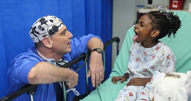 Image of a little girl sticking her tongue out for her doctor.