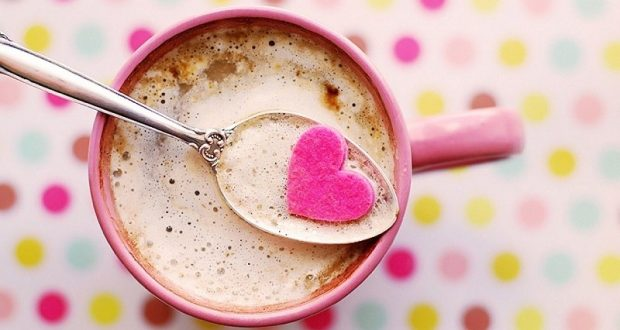 Image of a cup of hot chocolate with a pink candy heart on top.