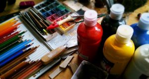 Image of an artist's table, with paint and colored pencils.