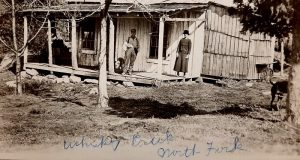 Nearly a century-old image of a couple on the front porch of a cabin.