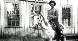 Antique image of cowboy on horseback in front of the Summerdale Hotel.