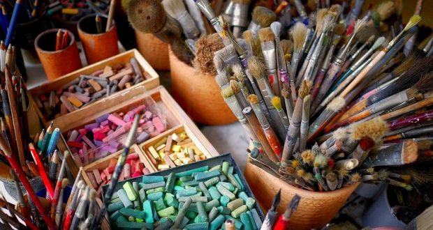 Image of paint brushes and pastel chalks.