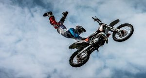 Image of a man riding a motorcycle through the air.