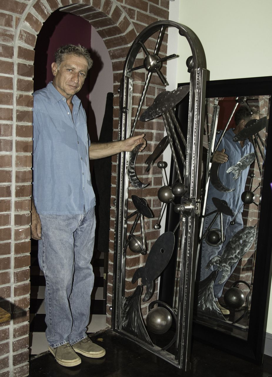 Moment Gallery - Owner Jeff Otto with his metal sculpted planetary door -  June 29 2013 - Photo by Virginia Lazar