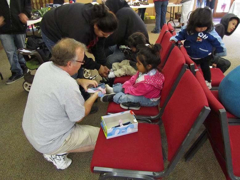 Pastor Steve fits kids with new shoes