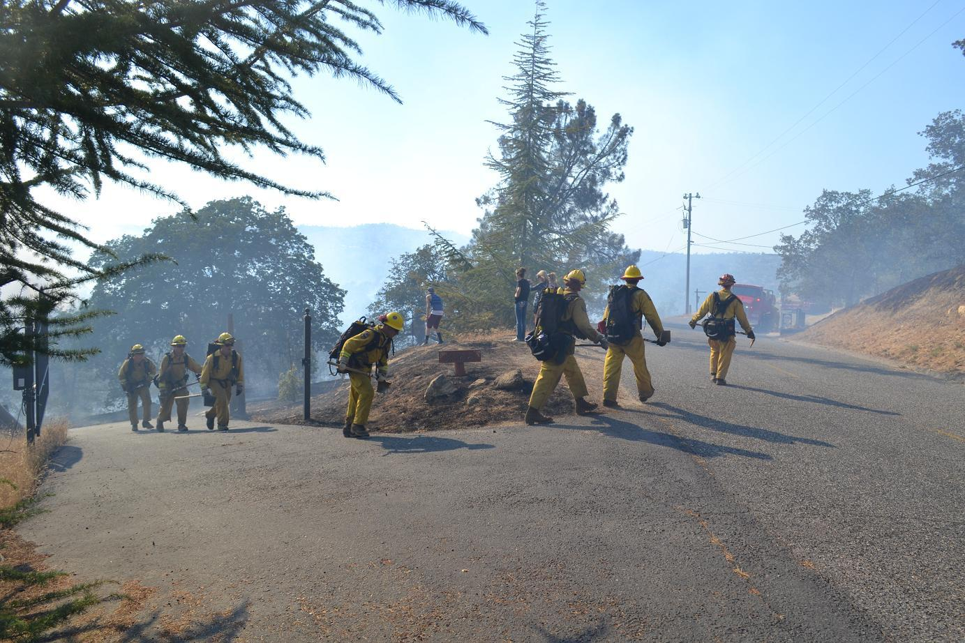 Firefighters hike up as residents watch the blaze