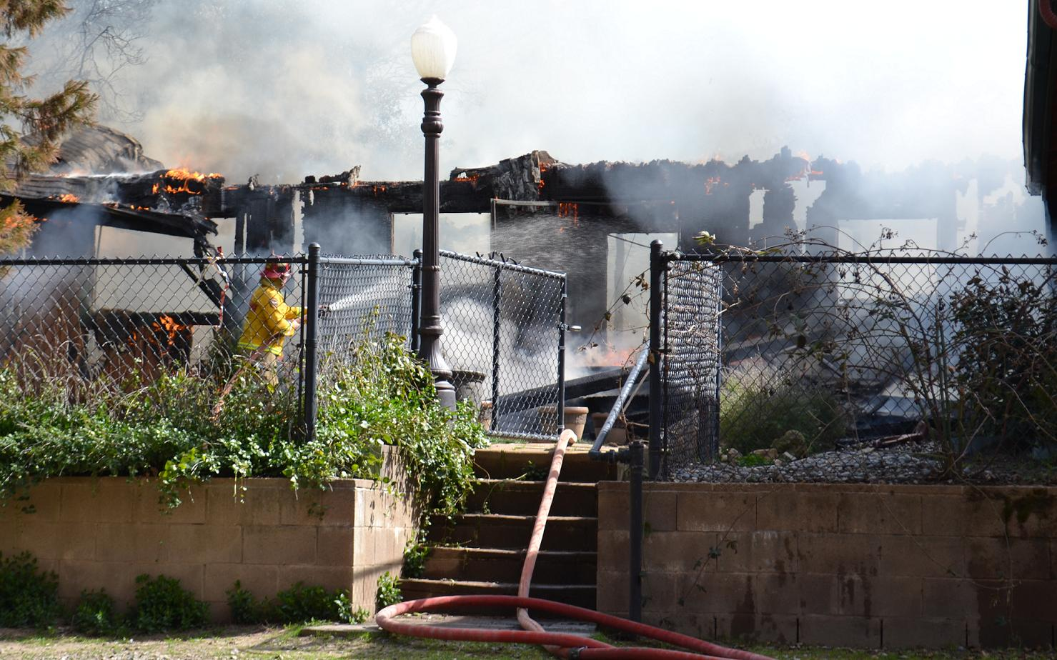 Firefighter hoses down whats left of the frame