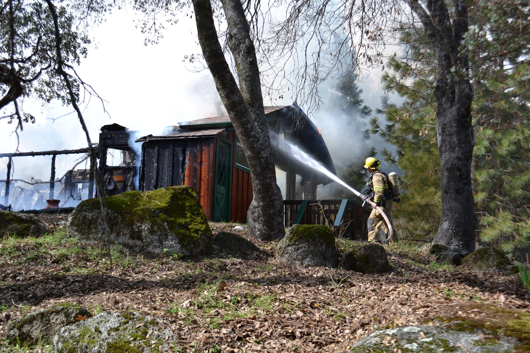 Firefighter works the side of the house