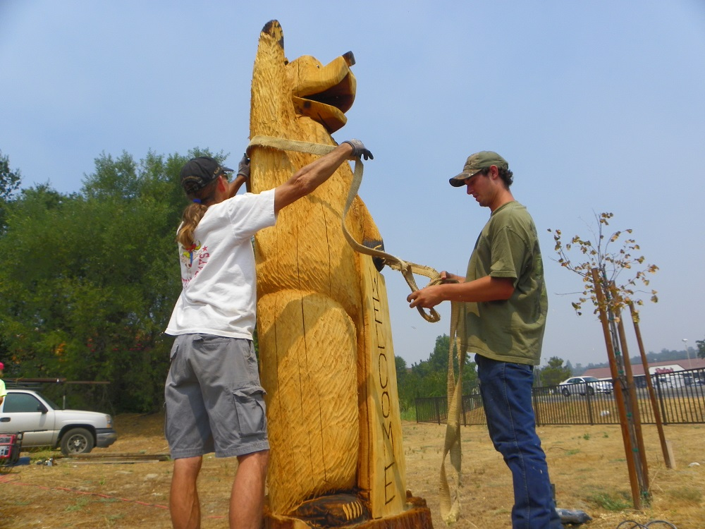 Carved Bear is put in place by crew at corner 41 49 - Photo by Kellie Flanagan