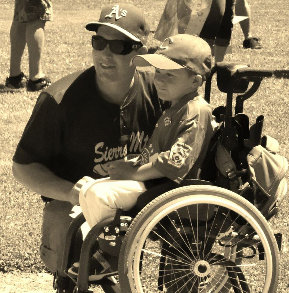 Photograph of Logan Sesto (seated) with his Challenger Division Little League Coach Jonas Garner