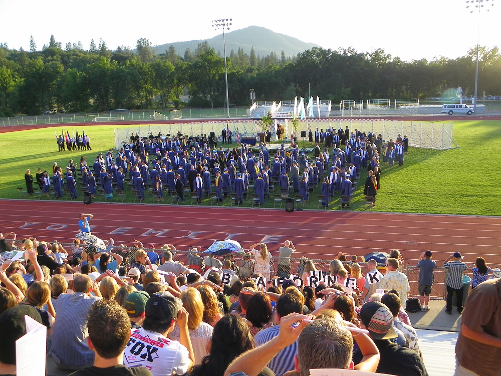Wide shot from bleachers as grads on field face stage at 2014 YHS  Graduation ceremony - photo by Clara Briley
