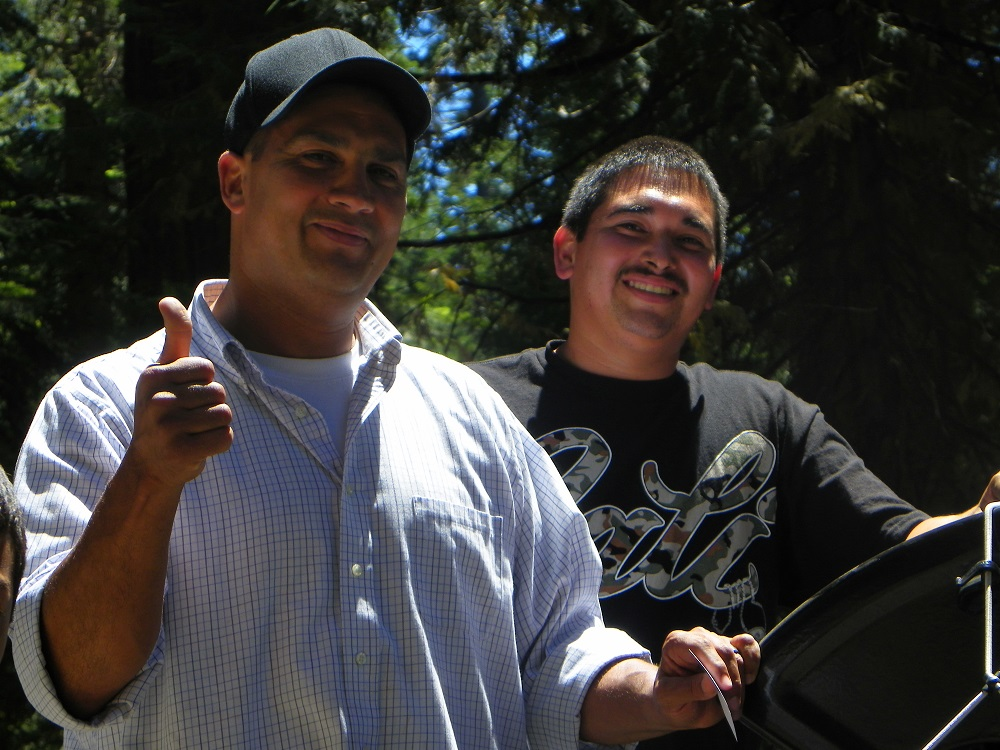 Men of the New Harvest Christian Fellowship in Madera give a thumbs up after their trailer after it was pulled back onto the road - photo by Kellie Flanagan