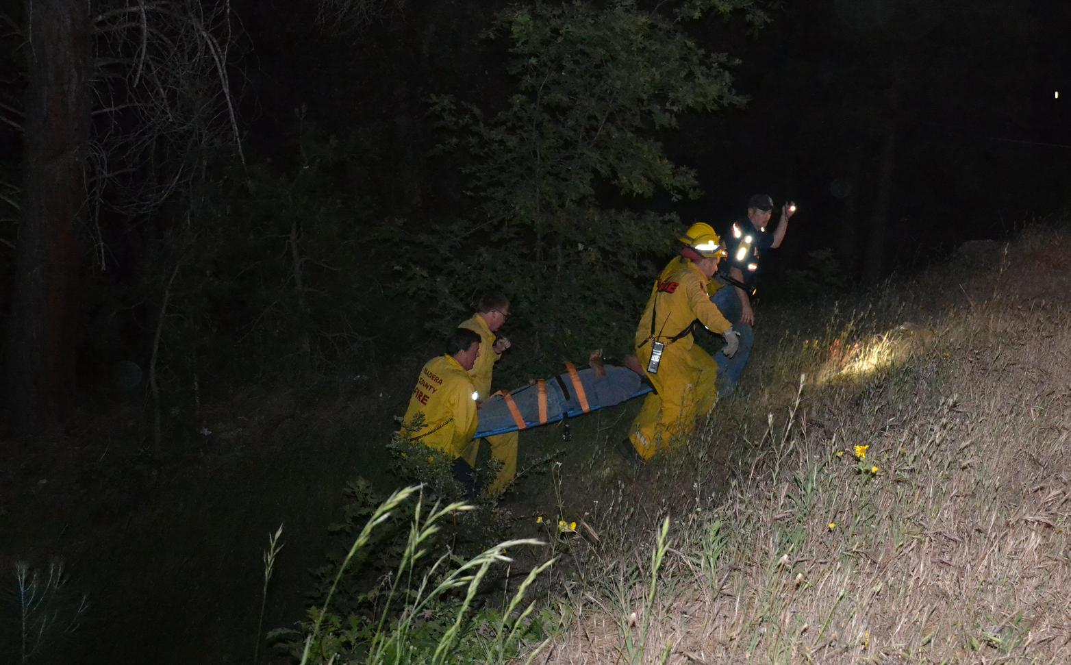 Rescuers carry accident victim up the embankment