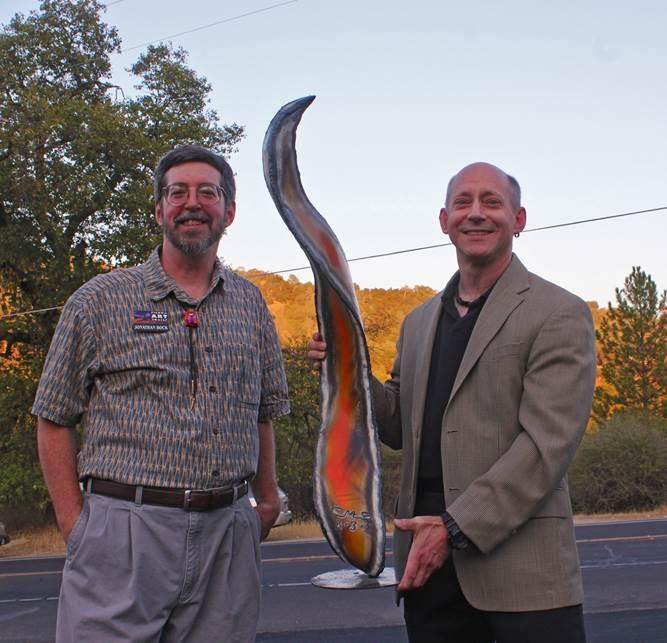 Jon Bock with the Sierra Art Trails (left) presents Children's Museum of the Sierra director Steve Montalto with the Keeper of the Flame award