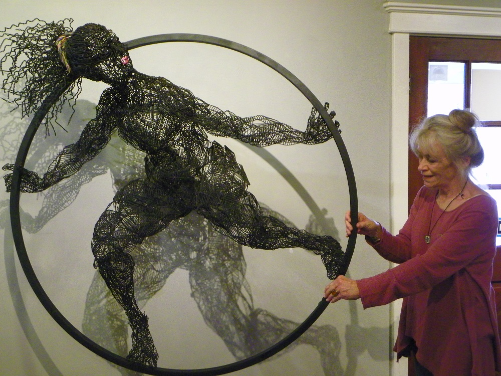 Wire Dancer figure by Evany Zirul as Julie Mitchell demonstrates the shadows cast by the piece - photo by Kellie Flanagan Feb 2015