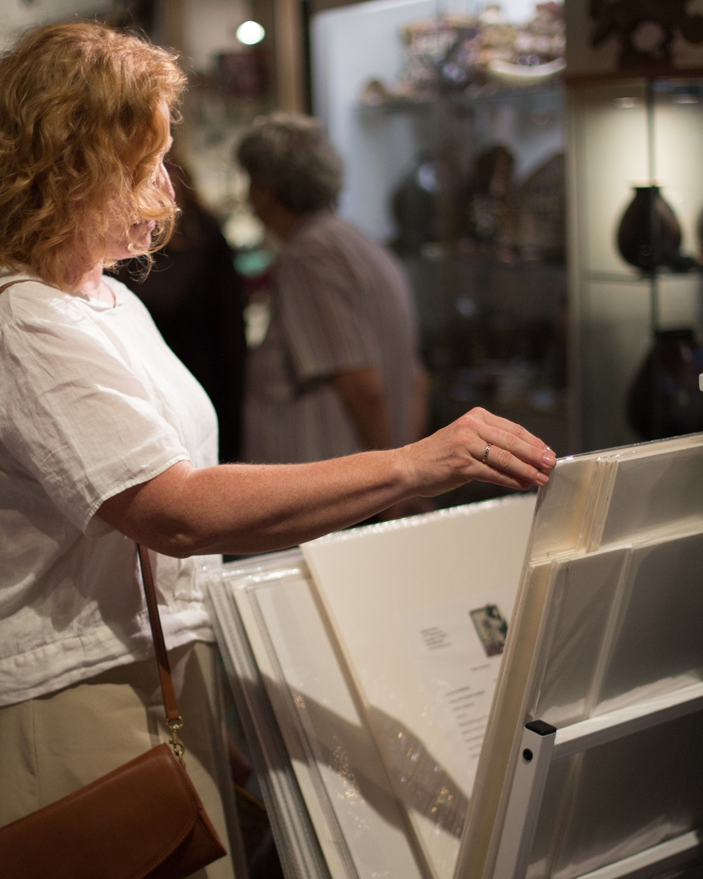Visitor to Sierra Art Trails open house peruses unframed gallery brings - photo by Virginia Lazar