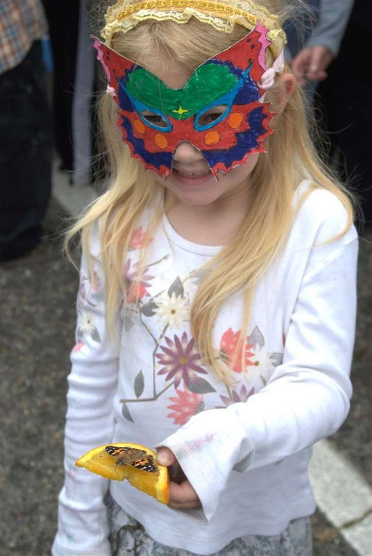 Mariposa Butterfly Festival - Child in mask holds butterfly - Photo courtesy of Charles Phillips Stone Creek Gallery Mariposa