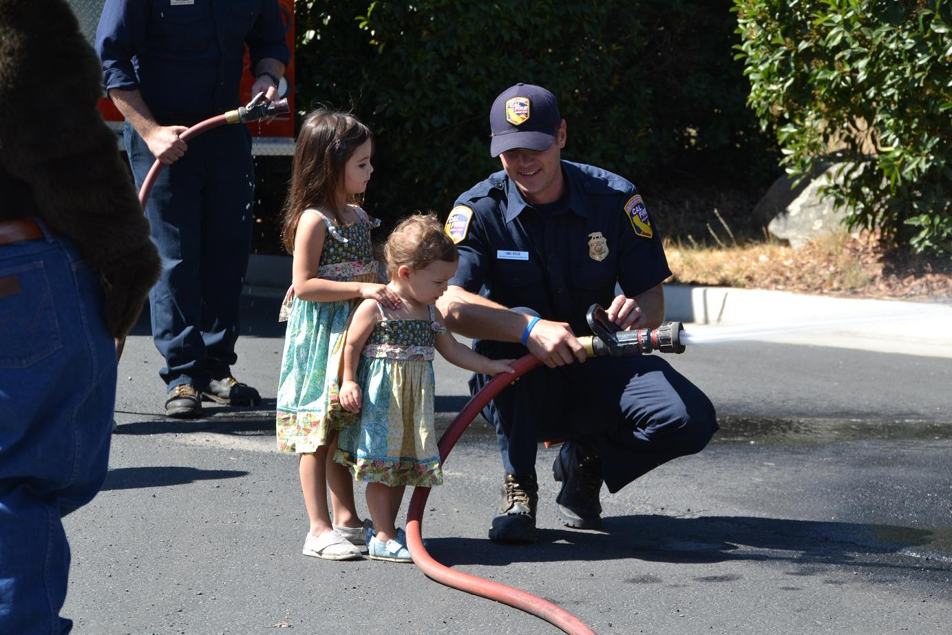 Firefighter Chris Butler shows kids how to use the fire hose - photo by Gina Clugston