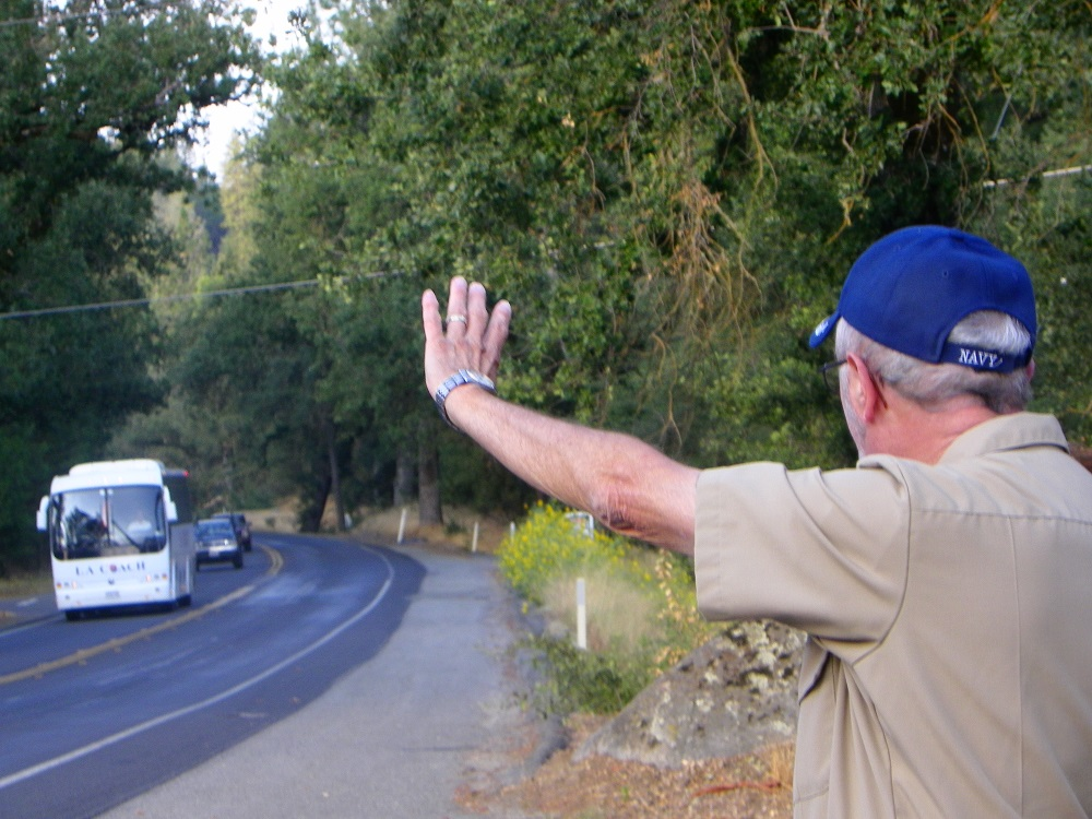 Waving Man Bill Briggs waves at a bus - 2013 - photo by Kellie Flanagan